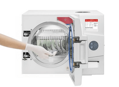 Steam Autoclave, person with gloves inserts packaged tools