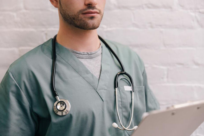 Health care professional in scrubs, with notepad and stethoscope